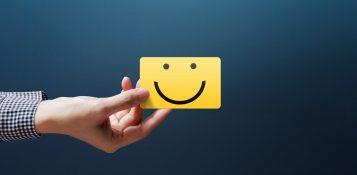 Person's hand with a happy face business card